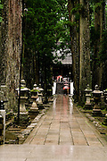 Monks with red laquered umbrellas leaving the main shrine.