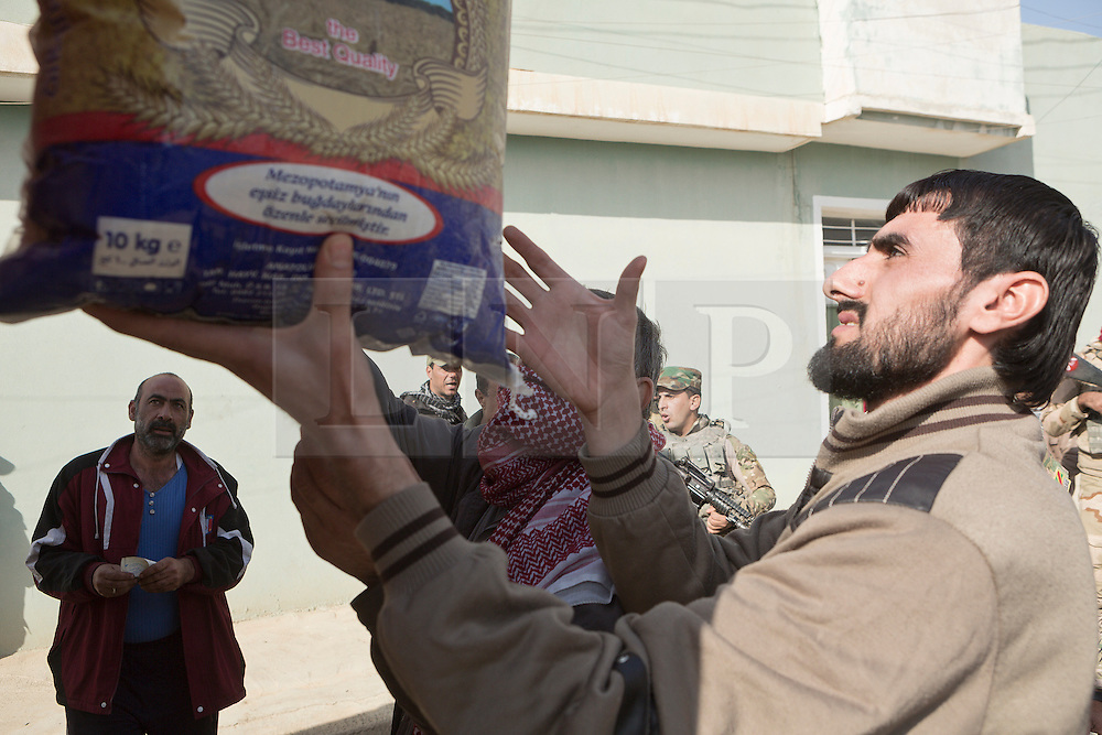Licensed to London News Pictures. 11/11/2016. Mosul, Iraq. A resident of Mosul's Al Antisar district receives a sack of food from a local volunteer. The Al Intisar district was taken four days ago by Iraqi Security Forces (ISF) and, despite its proximity to ongoing fighting between ISF and ISIS militants, many residents still live in the settlement without regular power and water and with dwindling food supplies.<br /> <br /> The battle to retake Mosul, which fell June 2014, started on the 16th of October 2016 with Iraqi Security Forces eventually reaching the city on the 1st of November. Since then elements of the Iraq Army and Police have succeeded in pushing into the city and retaking several neighbourhoods allowing civilians living there to be evacuated - though many more remain trapped within Mosul.  Photo credit: Matt Cetti-Roberts/LNP