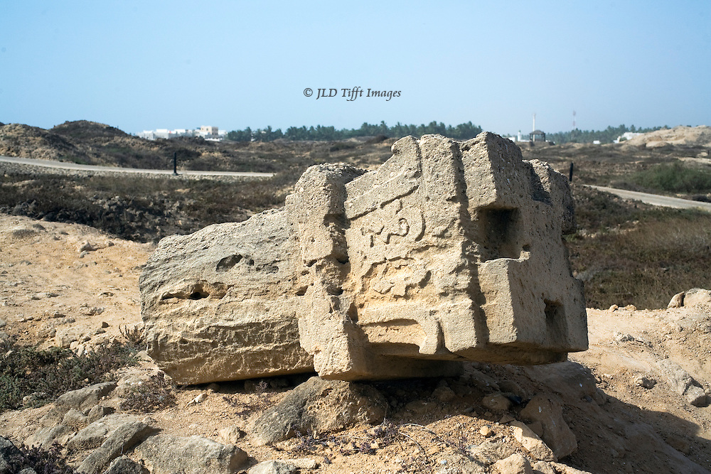 Views of the archaeological site at Al Baleed, part of UNESCO's Land of Frankincense preservation area.  Carved stone column capital lies on the ground.