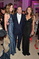 Left to right, TRINNY WOODALL, CHARLES SAATCHI and ELIZABETH HURLEY at the QBF Spring Gala in aid of the Red Cross War Memorial Children's Hospital hosted by Heather Kerzner and Jeanette Calliva at Claridge's, Brook Street, London on 12th May 2015.