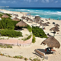 Playa Delfines in Cancun, Mexico<br /> At the KM marker 18 is Playa Delfines, a stretch of gorgeous sand with moderate surf. It has all the accoutrements needed for a glorious day in the sun &ndash; thatched umbrellas (palapas), lifeguards, restrooms, snack vendors, playground - yet less crowded than the northern beaches because there are no hotels lining the coast. The name means Dolphin Beach.  If you are lucky, you might see a pod swimming offshore. Perhaps this is why it is also called El Mirador meaning The Lookout.