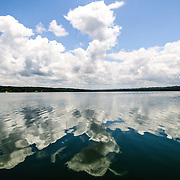 Clouds and sky reflected on the smooth surface of Lake Peten Itza near Flores, Peten, Guatemala.