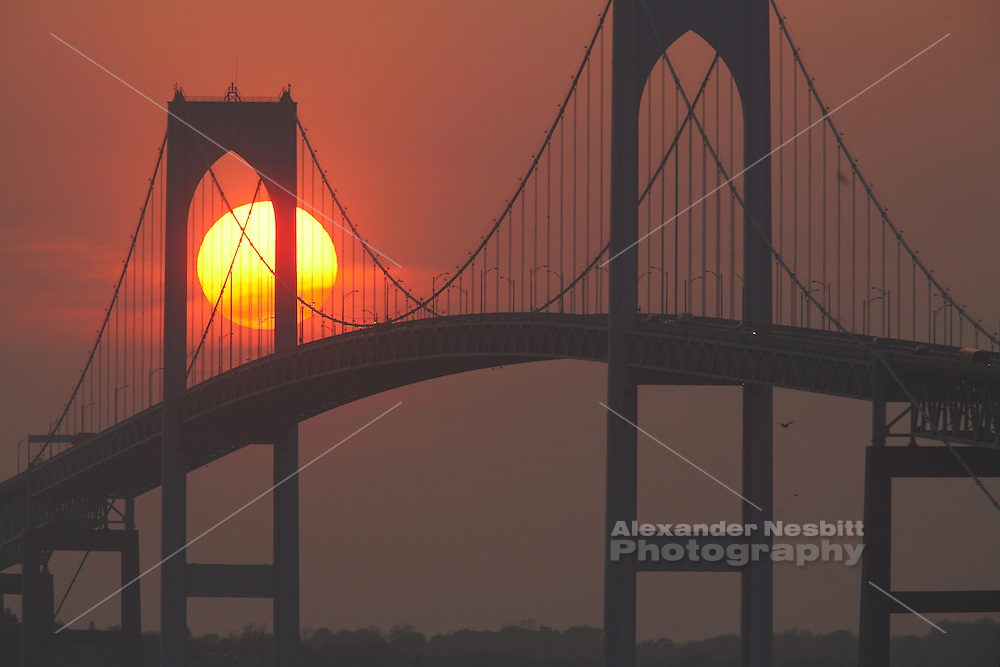 USA, Newport, RI - Sunset behind pilings of Newport Bridge.