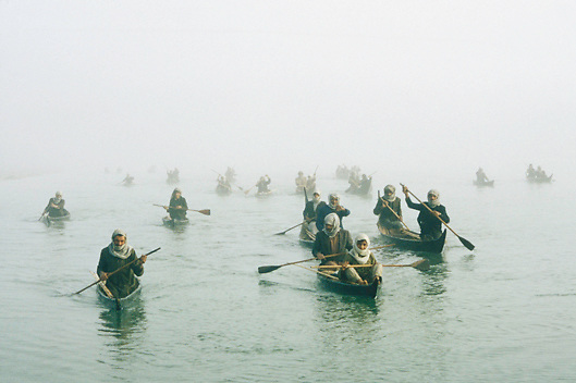 Marsh Arabs in the marshlands of Southern Iraq paddle their small canoes in early morning mist as they go off to fish or tend their fields