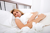 Woman suffering from abdomen pain in bed
