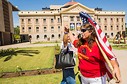 25 JUNE 2012 - PHOENIX, AZ:   MARTHA PAYAN (left) and ALLISON CULVER (red shirt) celebrate and picket the Arizona state capitol after the US Supreme Court overturned most of SB1070 Monday. Many conservatives in Arizona viewed the Court's decision as a victory because it let stand one small portion of the law. The case, US v. Arizona, determined whether or not Arizona's tough anti-immigration law, popularly known as SB1070 was constitutional. The court struck down most of the law but left one section standing, the section authorizing local police agencies to check the immigration status of people they come into contact with.      PHOTO BY JACK KURTZ