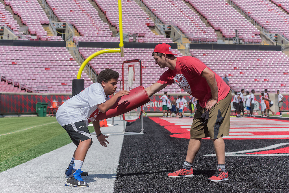 Donovan Pleasant, 13, an eighth-grader at Ramsey Middle School, has a one-on-one session with Gary Barnidge, a co-founder of the American Football Without Barriers youth football camp, during practice at the University of Louisville's Papa John's Cardinal Stadium. June 25, 2016