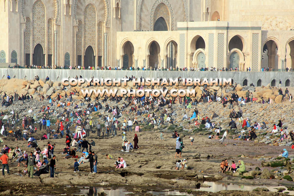 Crowd of Native Moroccans watching the Sunset by Hassan II Mosque and over the Atlantic Ocean, Casablanca, Morocco.