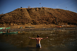 November 25, 2016 - Cannon Ball, North Dakota, U.S - A water protector opens his arms as he stands in the partially frozen Missouri River after authorities placed barbed wire along the river near Oceti Sakowin Camp at the Standing Rock Indian Reservation in Cannon Ball, North Dakota. Overnight, authorities placed barbed wire, confiscated and smashed water protector canoes and destroyed a makeshift bridge that was used to cross the river the day before during an action against the Dakota Access Pipeline. (Credit Image: © Joel Angel Ju‡Rez via ZUMA Wire)