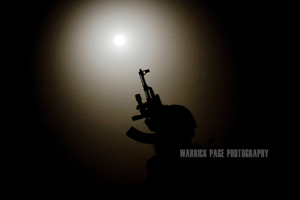 BAGHDAD, IRAQ - MAY 27: Iraqi Emergency Response Brigade (ERB) member is silhouetted in the moonlight as he watches over the perimeter while his unit searches the neighbourhood for a suspected insurgent responsible for planting IEDs, on May 27, 2010, on the outskirts of Baghdad, Iraq. Iraqi Special Forces and ERB and been training under US Special Forces for several years with a heavy focus on evidence collection and both legal and human rights for detained suspects. Members of the unit make little more than $700 a month and keep their identity a secret as many prevail from areas where insurgency is rife. US Special Forces are not permitted to accompany Iraqi ERB on missions unless an arrest warrant has been issued. Iraq faces multiple challenges in the lead-up to the drawn-down of US forces in Iraq, with many observers claiming that while they have the capablities of handling home-grown problems, they are far from being able to tackle external threats. Political wrangling has reportedly fostered greater instability throughout the country with fears of renewed sectarian violence breaking out as insurgents set-up attacks in an attempt to exploit vulnerabilities amongst the populace. (Photo by Warrick Page)