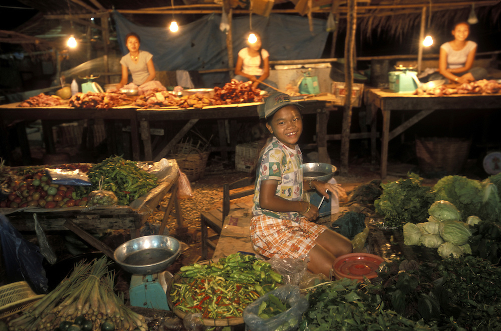 Asia, Laos, Vientiane, Young girl works at produce stand at night market northeast of capital city