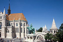 This view of Trinity Square includes the Matthias Church on left and the turrets of the Fisherman's Bastion on the right, on top of Buda Hill, Budapest, Hungary. Equestrian statue commemorates King (and Saint) Stephen; note that both a crown and a halo top his head.