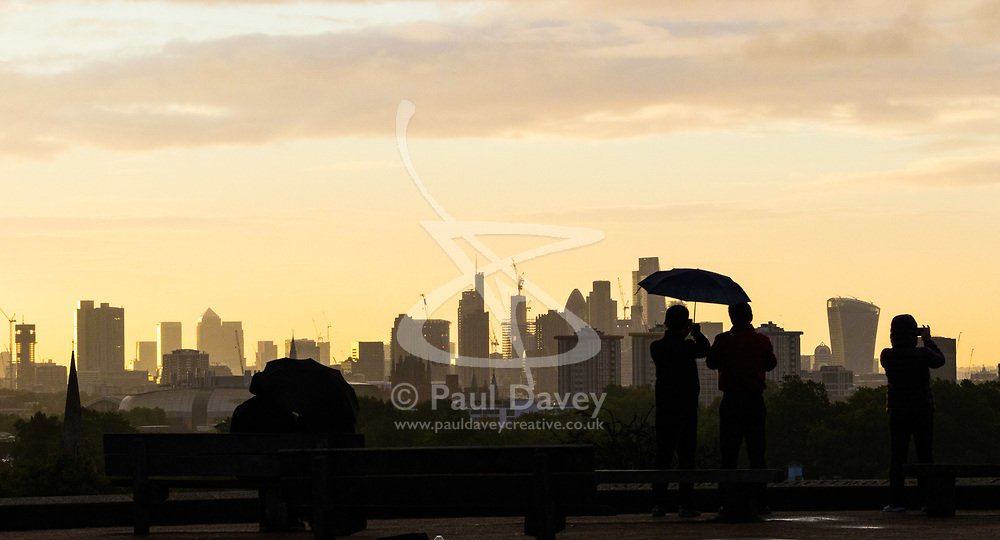 London, September 11 2017. People shelter from an early morning shower on Primrose Hill, admiring the London skyline as a new day breaks over the city. © Paul Davey