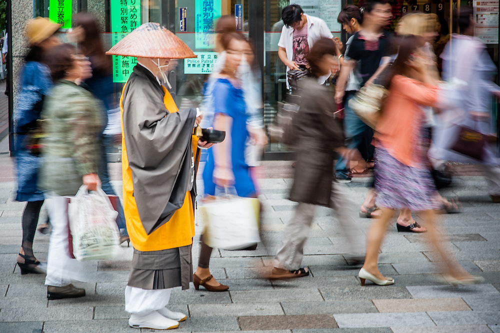 Buddhist monk meditating while walking in Tokyo's Ginza shopping district