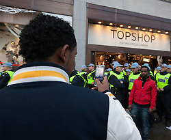 © Licensed to London News Pictures. 17/12/2011. LONDON, UK. Shoppers take pictures of Metropolitan Police Territorial Support Group (TSG) officers guarding the front of Topshop's flagship Oxford Street store from UK Uncut protesters in London today (17/12/11). Demonstrators had intended to hold a protest inside the shop, but the few that gained entry were ejected by security and police. Photo credit: Matt Cetti-Roberts/LNP