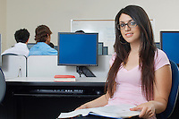 Female student sitting in computer classroom, portrait