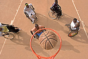 A group of handicapped basketball players score a point in the hoop during a basketball training session in Burkina Faso. This group is part of a project set up by Handicap Solidaire who are an NGO for disabled people.