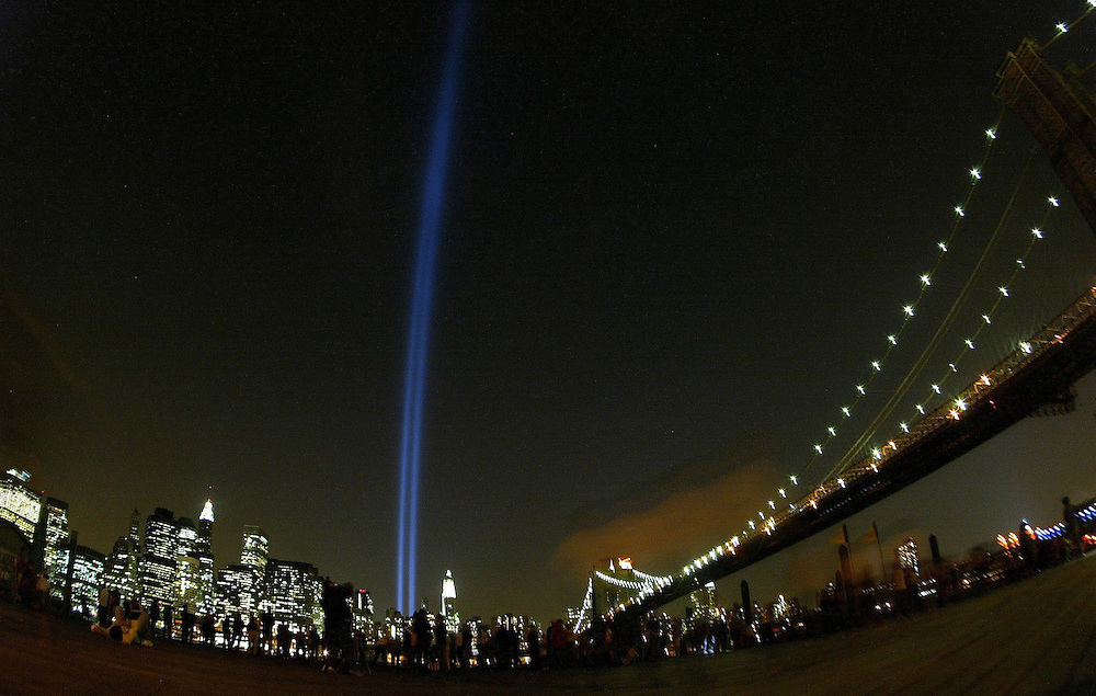 "The ""Tribute in Light"" beams shoot skyward from Ground Zero as seen from Brooklyn, NY alongside the Brooklyn Bridge (R) on the second anniversary of the attacks on the World Trade Center Thursday, 11 September, 2003 in New York City.Andrew GOMBERT"