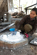 A woman works with others to pound cooked rice so that it can be pressed into noodles.