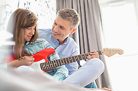 Happy father and daughter playing electric guitar at home