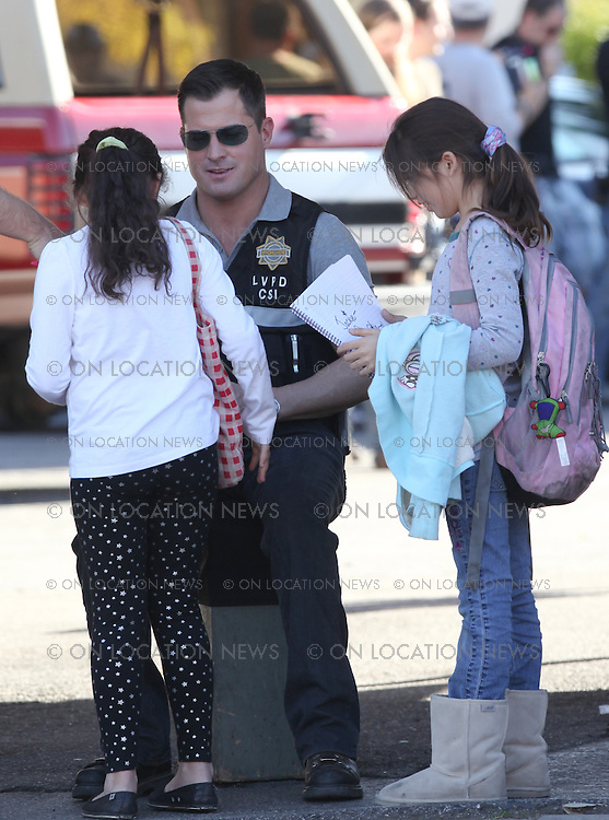 """***EXCLUSIVE***   January 13th 2009 Los Angeles, CA.  """"CSI: Crime Scene Investigation """" cast member George Eads who plays Nick Stokes sits down to sign autographs for two young girls who lived across the street from the filming location. Although the girls were waiting for an autograph from Taylor Swift, they were thrilled to talk to George who was very nice to the girls. Eric Ford/ On Location News 818-613-3955 info@onlocationnews.com"""