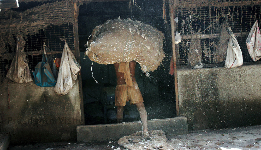 A labourer works at a cotton cleaning workshop in the Dharavi slums in Mumbai June, 18 2007.