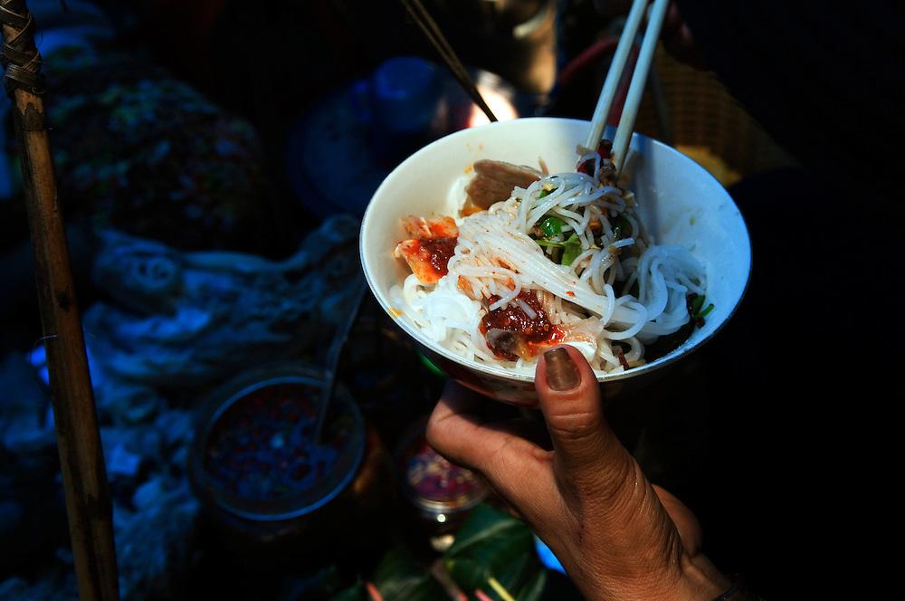 Vietnam: Hue<br /> A Vietnamese woman eating noodles, Dong Ba Market.