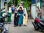 25 JUNE 2017 - BANGKOK, THAILAND:  A family walks to Ton Son Mosque for Eid al-Fitr prayers. Eid al-Fitr is also called Feast of Breaking the Fast, the Sugar Feast, Bayram (Bajram), the Sweet Festival or Hari Raya Puasa and the Lesser Eid. It is an important Muslim religious holiday that marks the end of Ramadan, the Islamic holy month of fasting. Muslims are not allowed to fast on Eid. The holiday celebrates the conclusion of the 29 or 30 days of dawn-to-sunset fasting Muslims do during the month of Ramadan. Islam is the second largest religion in Thailand. Government sources say about 5% of Thais are Muslim, many in the Muslim community say the number is closer to 10%.   PHOTO BY JACK KURTZ