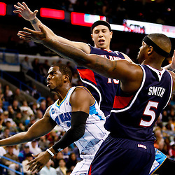 December 26, 2010; New Orleans, LA, USA; New Orleans Hornets point guard Chris Paul (3) shoots between Atlanta Hawks defenders point guard Mike Bibby (10) and power forward Josh Smith (5) during the third quarter at the New Orleans Arena.  The Hornets defeated the Hawks 93-86. Mandatory Credit: Derick E. Hingle