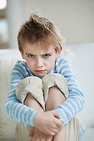 Portrait of young boy frowning while sitting on sofa