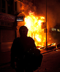 © Licensed to London News Pictures. 08/08/2011. LONDON, UK. Police stand in front of a burning shop on London Road in Croyden after it was set alight by rioters. The fire took place as Croydon was hit during a third night of violence across London which also spread to at least three other cities in the United Kingdom. Photo credit: Matt Cetti-Roberts/LNP