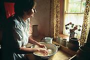 Ireland, Bunratty, Bunratty Folk Park, woman kneading dough at window in cottage