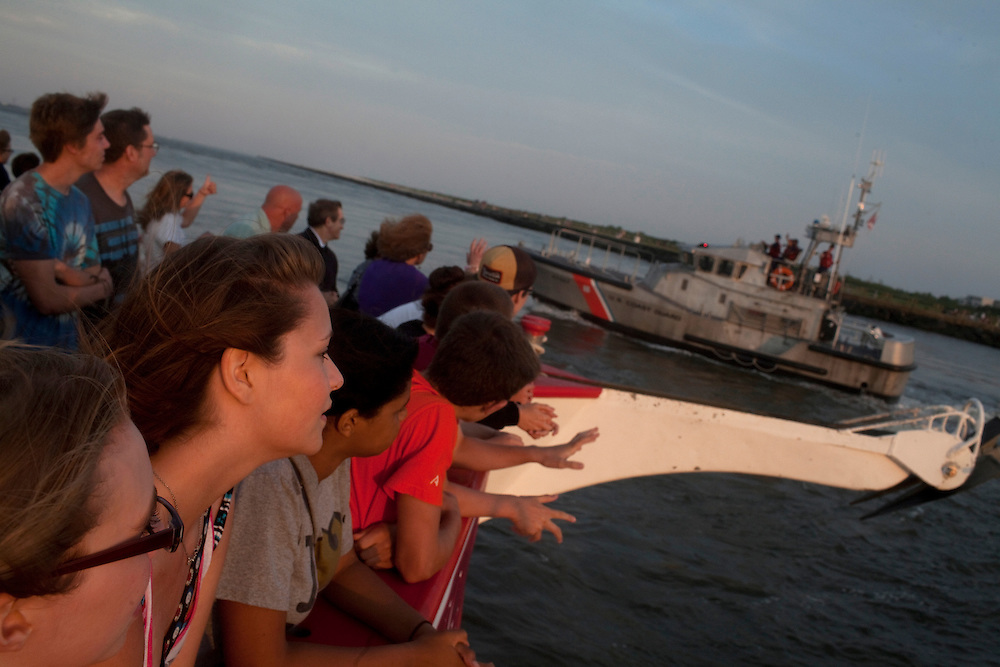 Long Beach Island, NJ - June 29, 2013 :  Visitors on Miss Barnegat Light sunset cruise wave to the coastguard on the northern tip of Long Beach Island, NJ on June 29, 2013. People are returning to the beaches for the summer after recovery efforts post Superstorm Sandy.