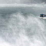 The Maid of the Mist boat emerges through teh spray at Niagara Falls on the Niagara River on the border between the United States and Canada.