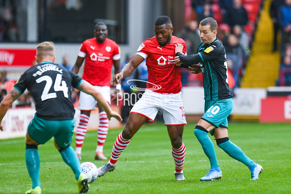 Barnsley defender Dimitri Cavare (12) and Swansea City midfielder Bersant Celina (10) in action during the EFL Sky Bet Championship match between Barnsley and Swansea City at Oakwell, Barnsley, England on 19 October 2019.