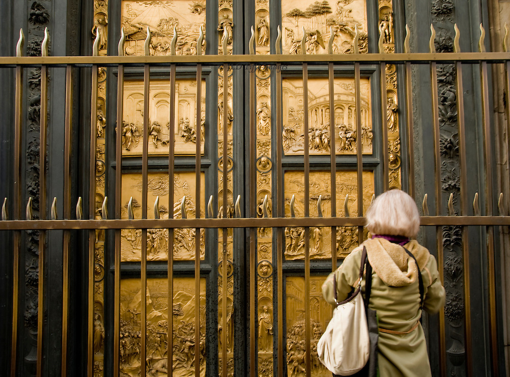 """Woman tourist with white or blonde hair looking through the protective fence in front of Ghiberti's """"Gates of Paradise"""", Florence Baptistry.  The in situ panels are copies, while the originals are in the Museo dell'Opera del Duomo being restored."""