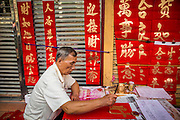 """09 FEBRUARY 2013 - BANGKOK, THAILAND:  A calligrapher draws New Years greetings for people in Chinatown in Bangkok. Bangkok has a large Chinese emigrant population, most of whom settled in Thailand in the 18th and 19th centuries. Chinese, or Lunar, New Year is celebrated with fireworks and parades in Chinese communities throughout Thailand. The coming year will be the """"Year of the Snake"""" in the Chinese zodiac.   PHOTO BY JACK KURTZ"""