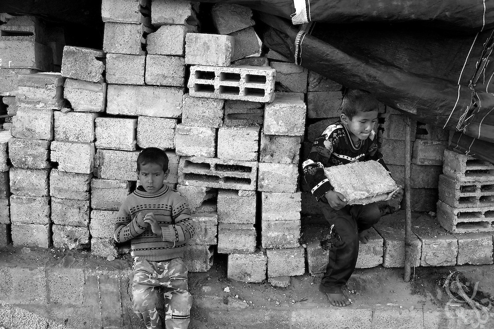 Palestinian children from the al-Bahabsa family carry recycled cinder blocks December 15, 2009 to help their father rebuild the family compound that was destroyed by the Israelis in the month long offensive a year ago in the Juhor al-Dik neighborhood southeast of Gaza City. A year after the Israeli military launched the controversial 22 day long Operation Cast Lead offensive against Gaza, Palestinians across the tiny strip continue to struggle daily in various ways economically, physically, and emotionally. .