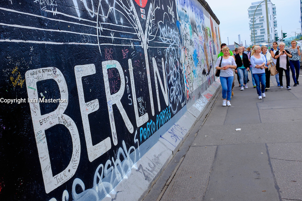 tourists walk past historic Berlin Wall remaining section at East Side gallery with many painted murals and graffiti in Friedrichshain Berlin Germany