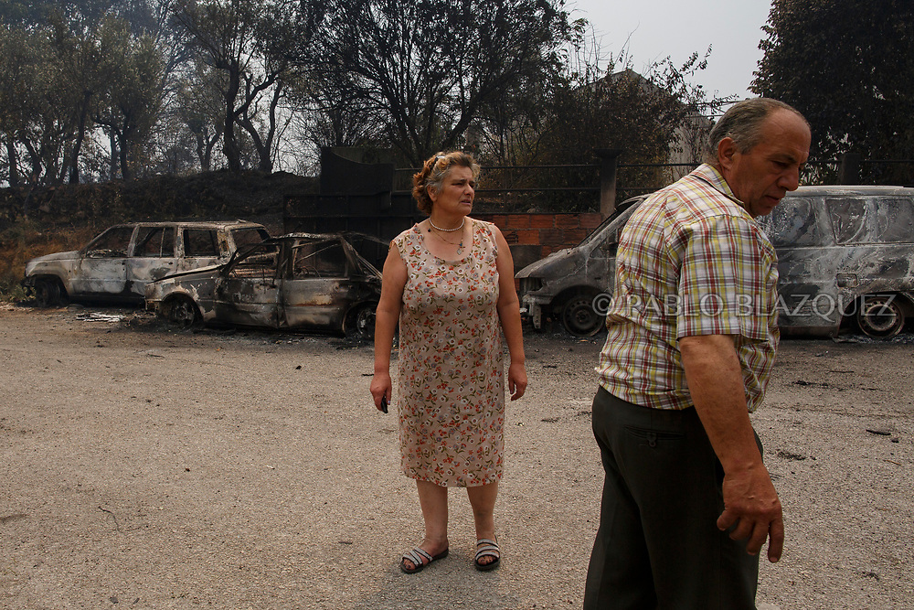 LEIRIA, PORTUGAL - JUNE 19:  A couple find damages at their return home after a wildfire took dozens of lives on June 19, 2017 near Castanheira de Pera, in Leiria district, Portugal. On Saturday night, a forest fire became uncontrollable in the Leiria district, killing at least 62 people and leaving many injured. Some of the victims died inside their cars as they tried to flee the area.  (Photo by Pablo Blazquez Dominguez/Getty Images)