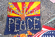 "An Arizona and U.S. flag with stones spelling ""practice peace"" is seen at the memorial outside the offices of congresswoman Gabrielle Giffords in Tucson, Arizona January 11, 2011. REUTERS/Rick Wilking (UNITED STATES)"