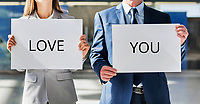 Business couple holding white placard with I love you sign