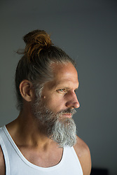portrait of a middle aged man with a beard and hair in a bun