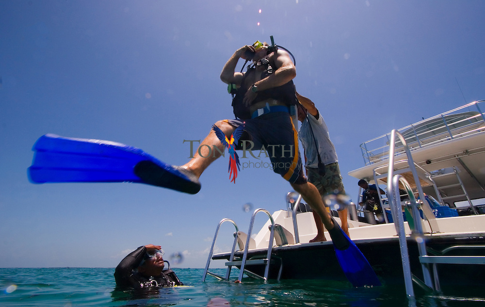 SCUBA diver doing a  giant stride entry into water as part of the Discover SCUBA Diving program at Hugh Parkey's Belize Dive Connection, Belize