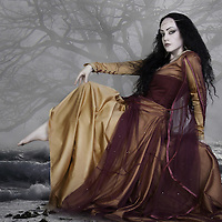 Medieval woman with long black hair sat outdoors in water and mist