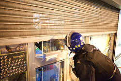 © Licensed to London News Pictures. 08/08/2011. Enfield, UK. Police come to the aid of a shopkeeper, hiding inside his shop, after his premesis is smashed whilst he's inside, during another night of rioting and looting across London. Photo credit : Joel Goodman/LNP