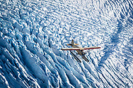 Air to air aerial photo of a classic 1933 Stinson SR JR floatplane flying over grewingk glacier in the Kenai Mountains, Alaska.