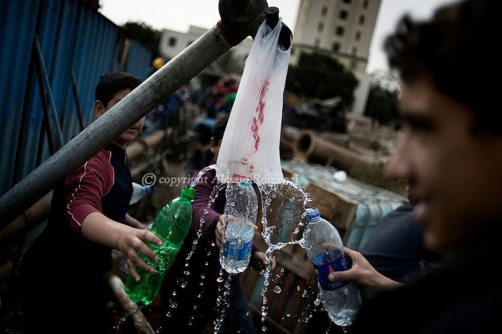 Children refill of water plastic bottles in Tahrir square in Cairo on February 04, 2010.© ALESSIO ROMENZI