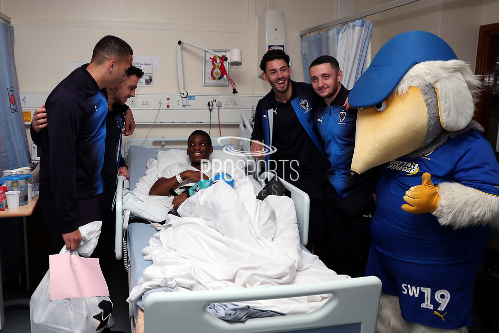 AFC Wimbledon attacker Egli Kaja (21), AFC Wimbledon defender Rod McDonald (26), AFC Wimbledon defender Will Nightingale (5), AFC Wimbledon midfielder Anthony Hartigan (8) and Haydon the Womble delivering Christmas presents to the children on behalf of AFC Wimbledon, at St George's Hospital, Tooting, United Kingdom on 13 December 2018.