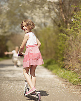 Young girl riding scooter in park away from camera to mother